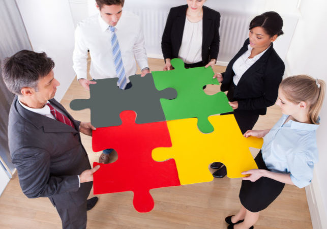 High Angle View Of Businesspeople Holding Multi Coloured Jigsaw Puzzle